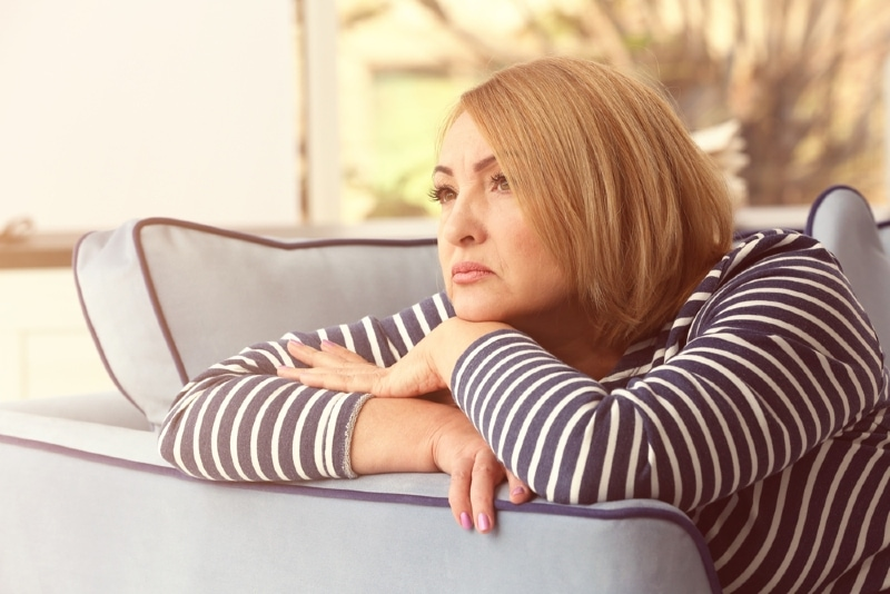 sad woman in striped top leaning on sofa