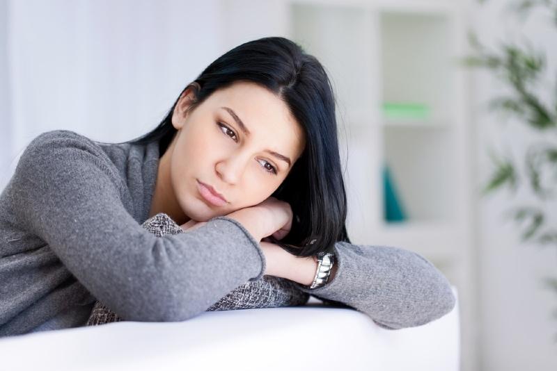 sad woman in gray sweater leaning on sofa