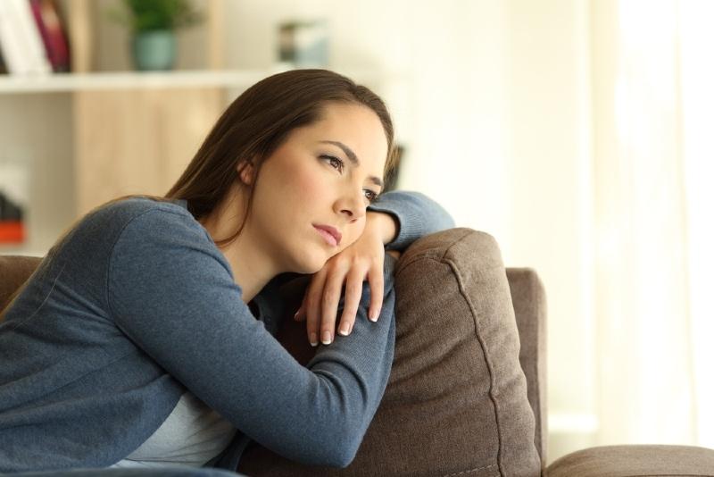 sad woman leaning on brown sofa