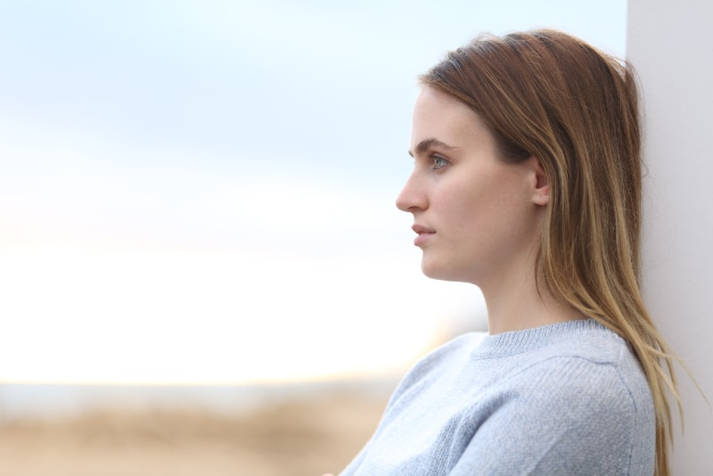 pensive woman in gray sweater leaning on wall outdoor