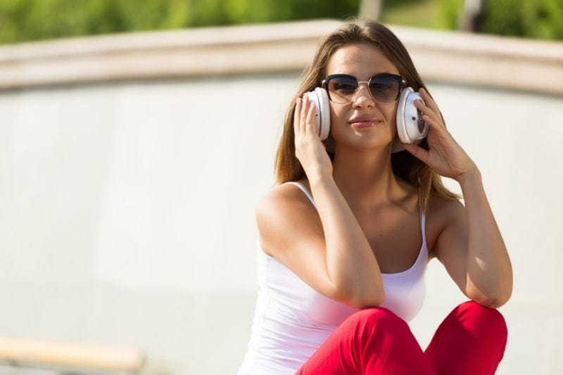 woman listening to music thru earphones sitting outdoors