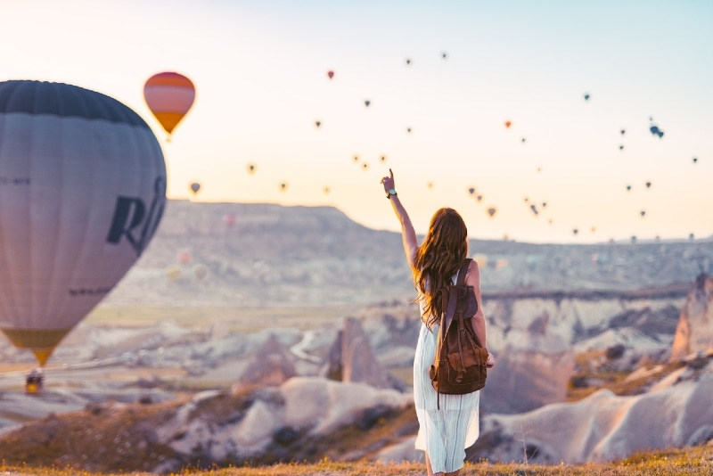 woman with brown backpack looking at hot air balloons
