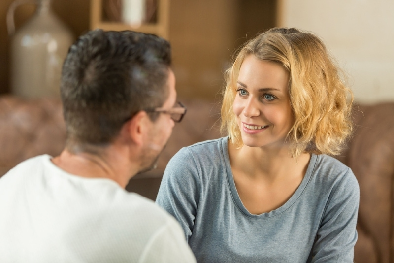 blonde woman looking at man while sitting indoor