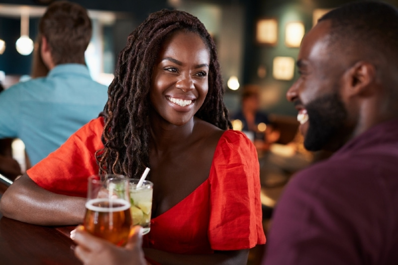 woman looking at man while sitting in bar
