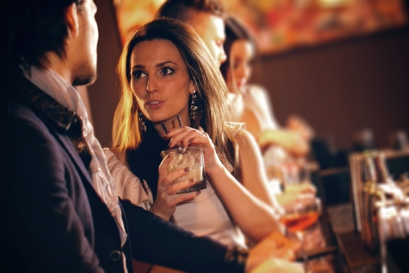 woman looking at man while holding drink in cafe