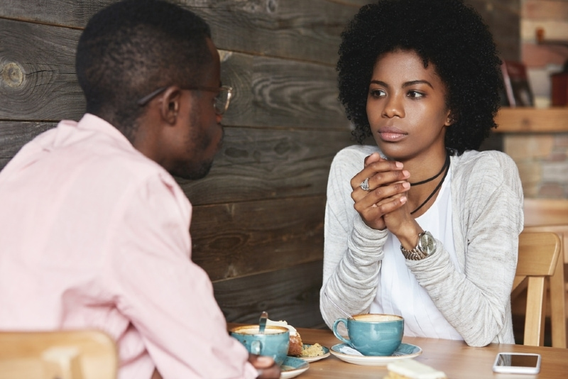 serious woman looking at man while sitting at table