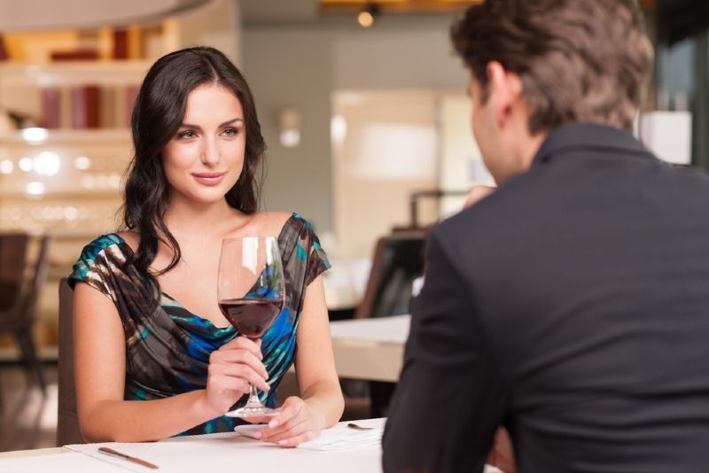woman looking at man while holding glass of wine