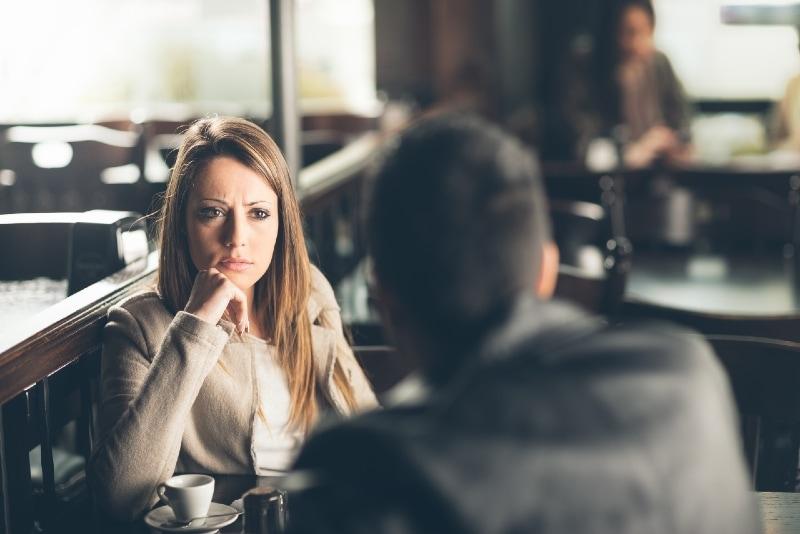 sad woman looking at man while sitting at table