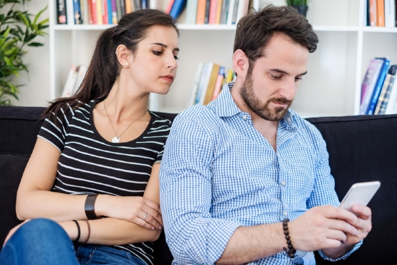 jealous woman looking at man's phone while sitting on sofa