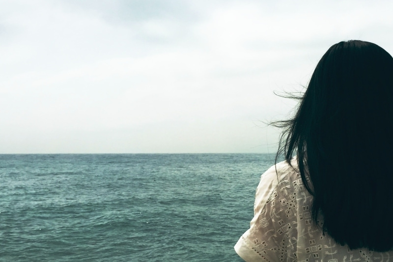 woman in white top looking at sea