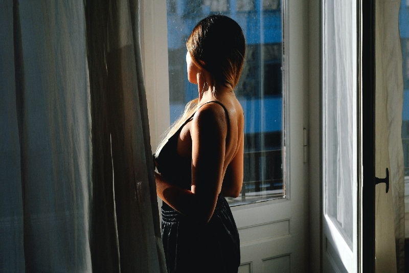 woman in black top looking outside