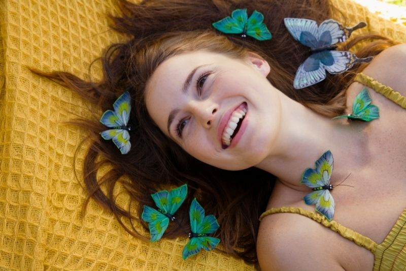 woman lying down and laughing with the butterflies around her head