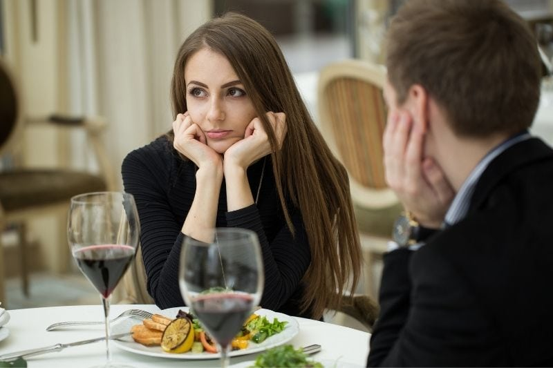 woman making exasperated expression during a dinner date with a man