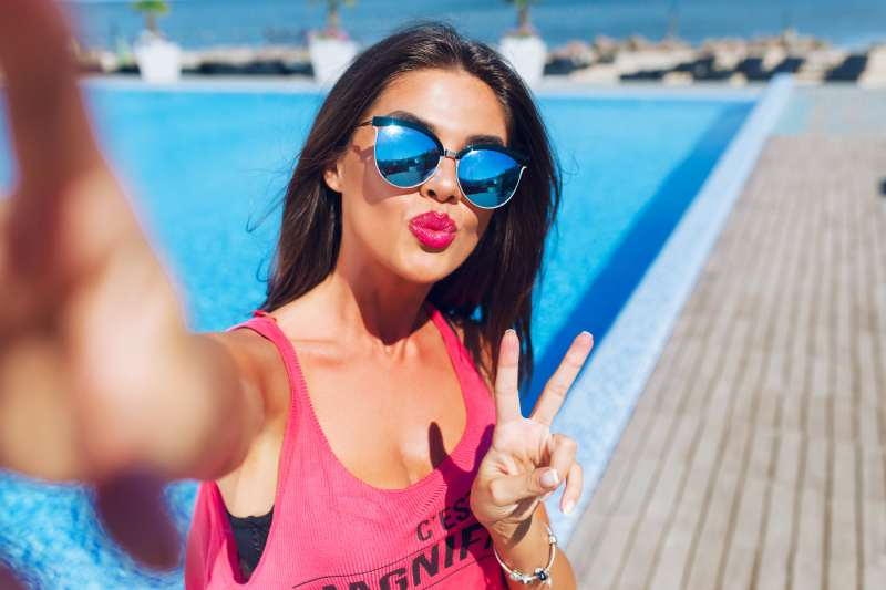 woman on vacation taking a selfie near the swimming pool