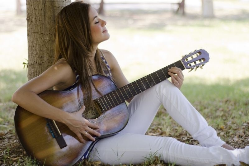 woman playing guitar alone under a tree in the park sitting on the ground