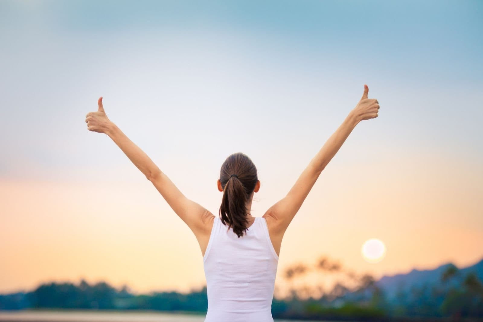woman raising hands with ok hand sign facing sunrise in rear view