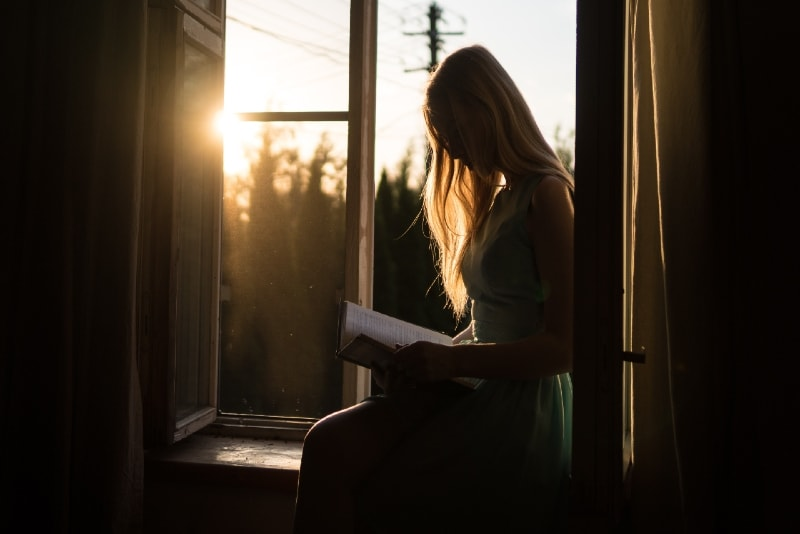 blonde woman reading book while sitting on window pane