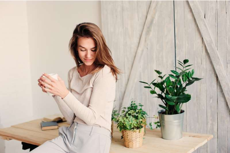 woman relaxing at home while drinking coffee wearing casual fashion clothes