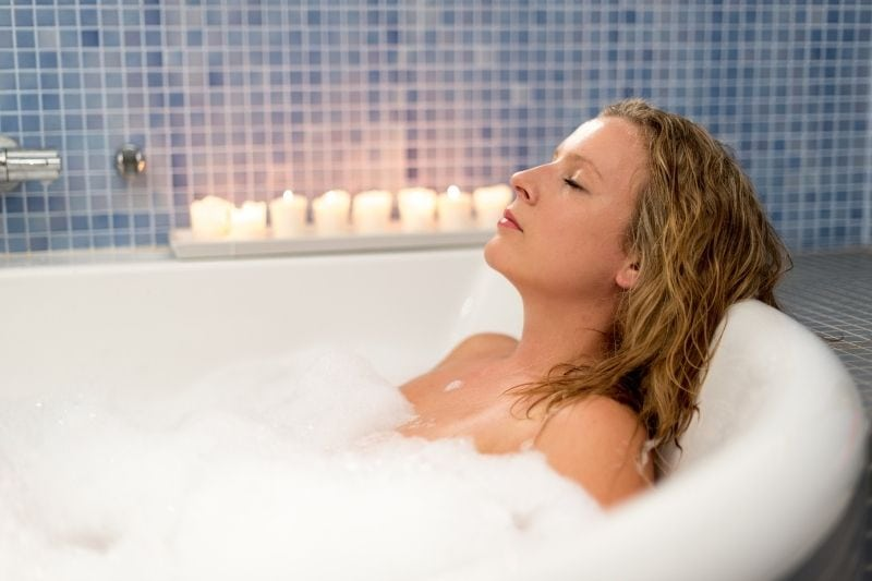 woman relaxing in bath tub closing her eyes with candles on the side