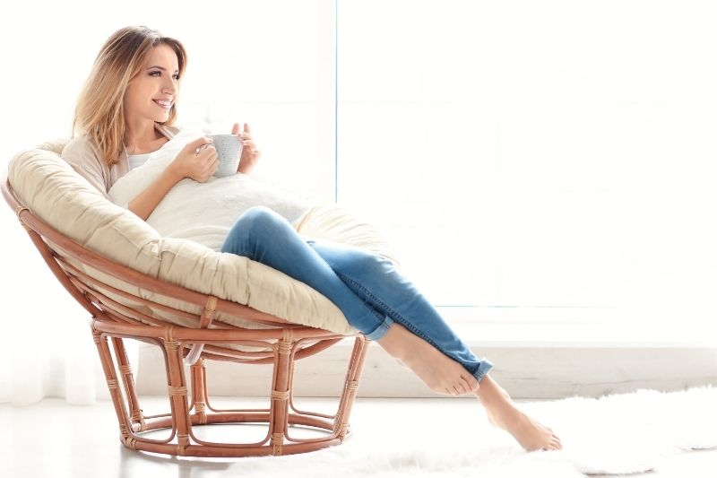woman relaxing in couch drinking coffee near the windows during the day