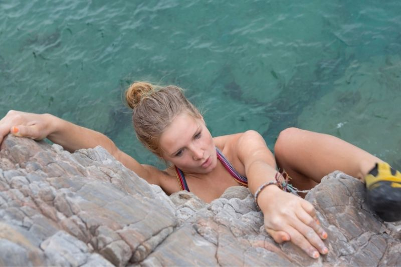 woman rock climbing a mountain with a body of water beneath on a top angle