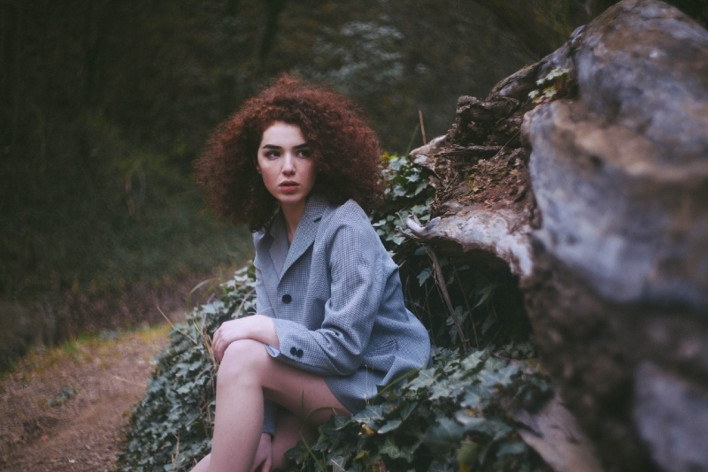 woman with curly hair sitting in forest