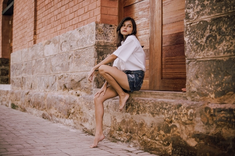 woman in white shirt sitting near old stone building