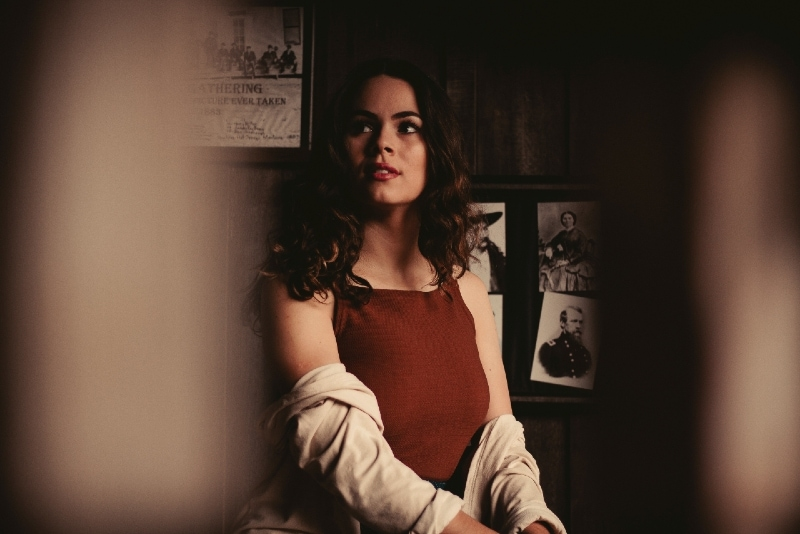 pensive woman with curly hair sitting near wall