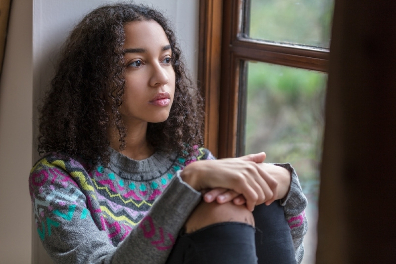 woman with curly hair sitting near window