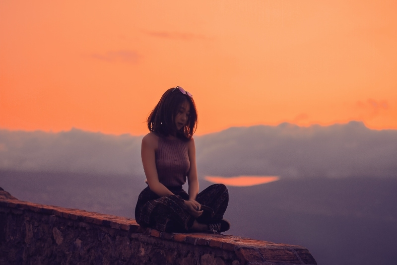 woman sitting on concrete surface during sunset