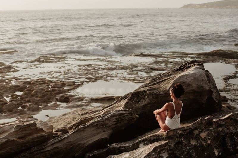 woman in white swimsuit sitting on rock looking at sea