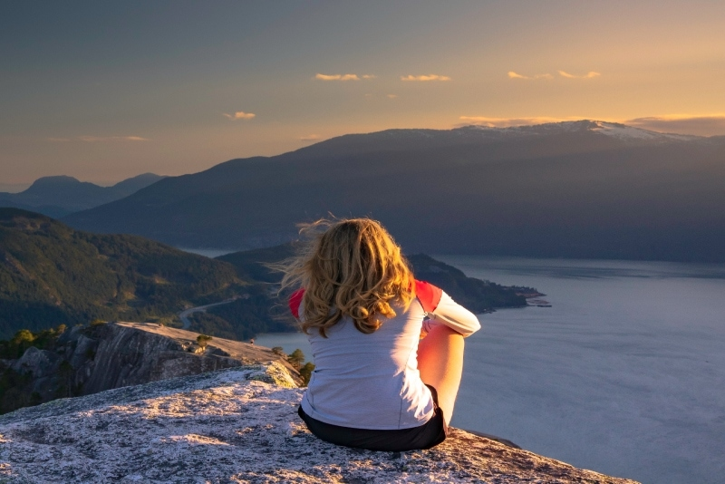 woman sitting on rock looking at mountain