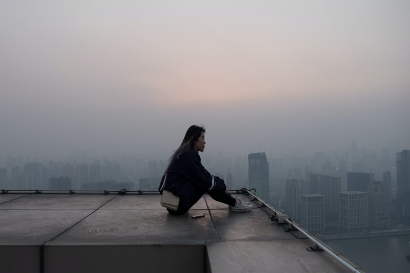 woman sitting on rooftop looking at buildings