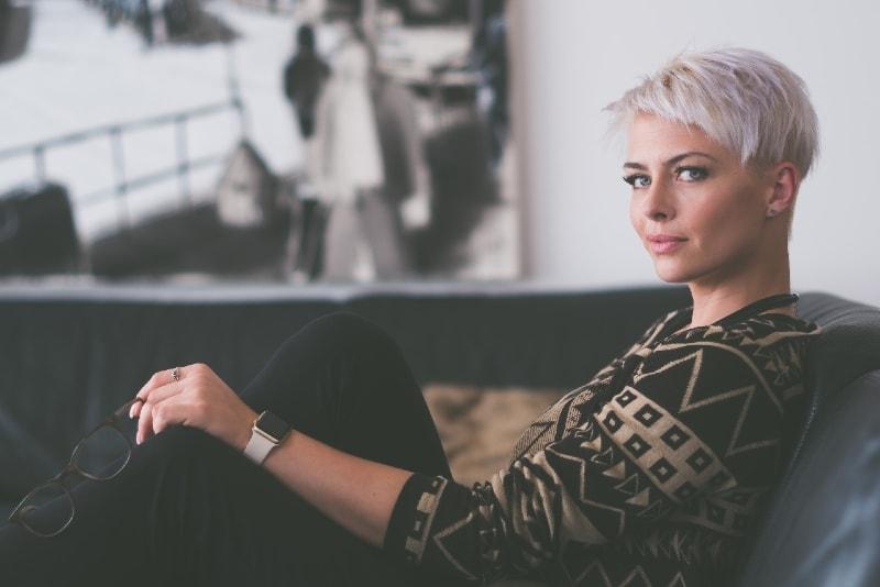 woman holding eyeglasses while sitting on sofa