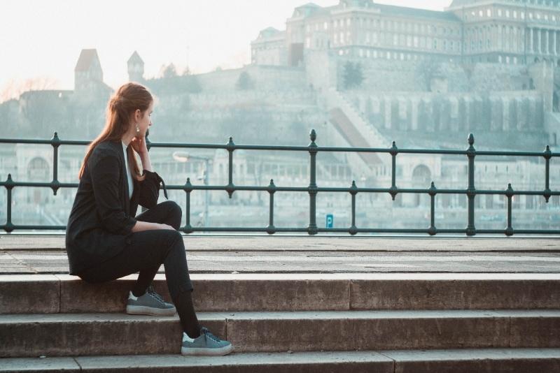 woman in black blazer sitting on stairs