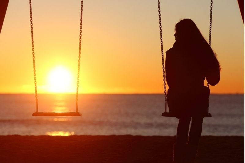 woman sitting on swing looking at an empty swing beside facing the sunset above the sea