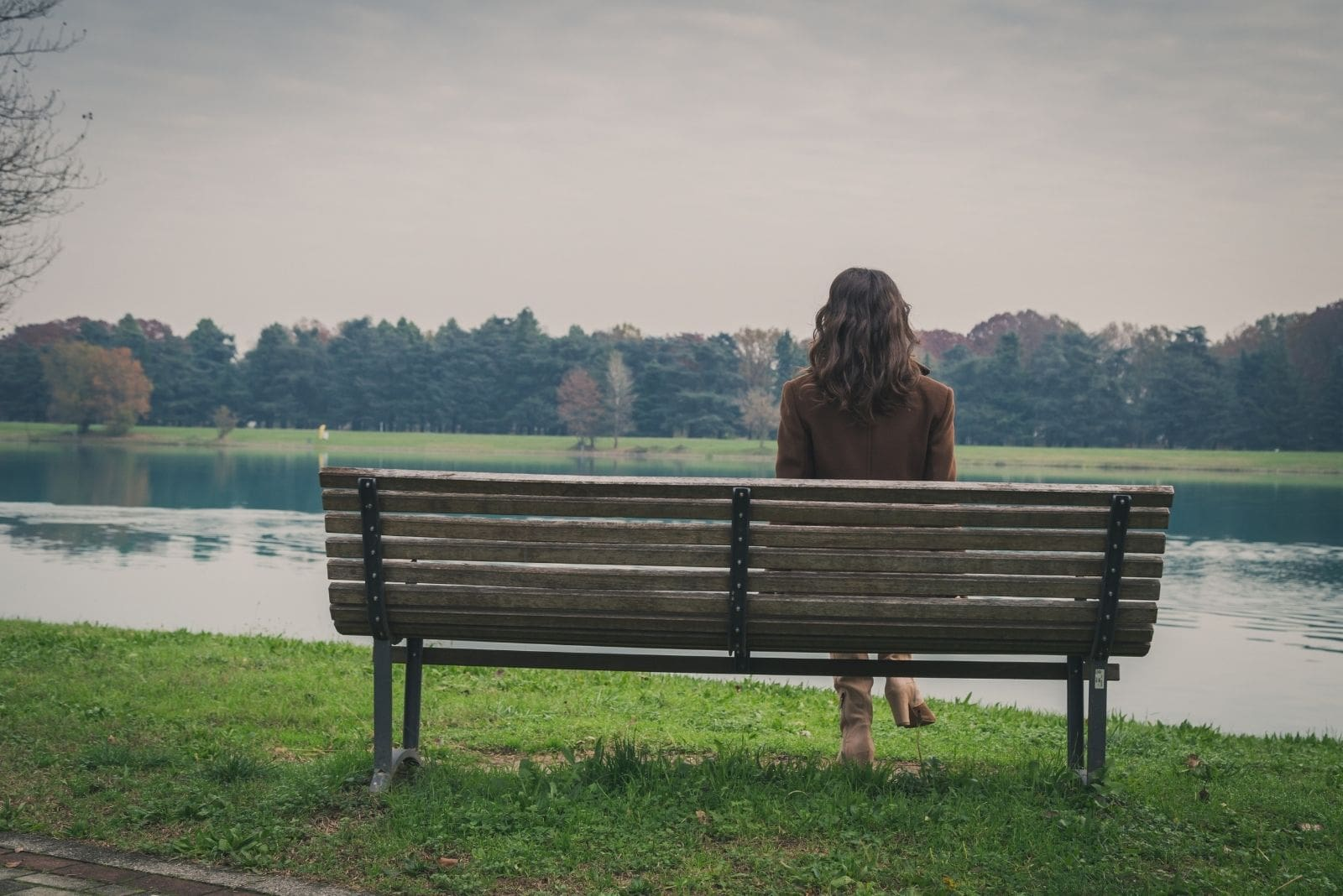 woman sitting on the bench facing the lake in solitude