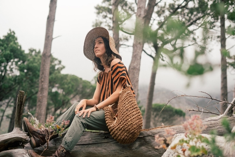 woman with hat sitting on wood log