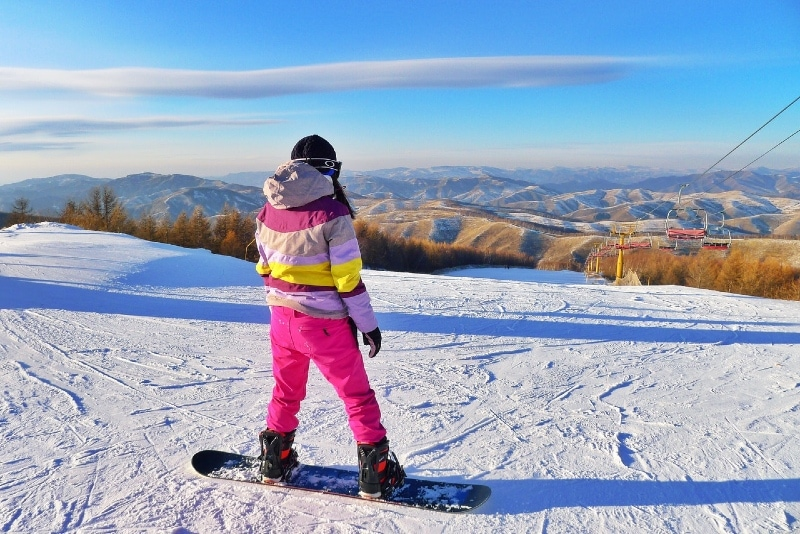 woman in pink pants snowboarding