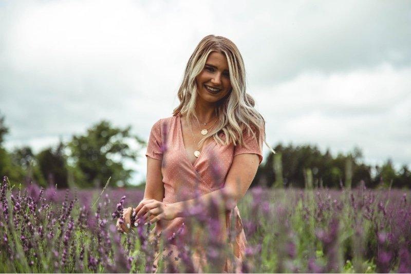 happy woman standing in purple flowers field