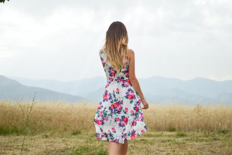 woman in floral dress standing in field