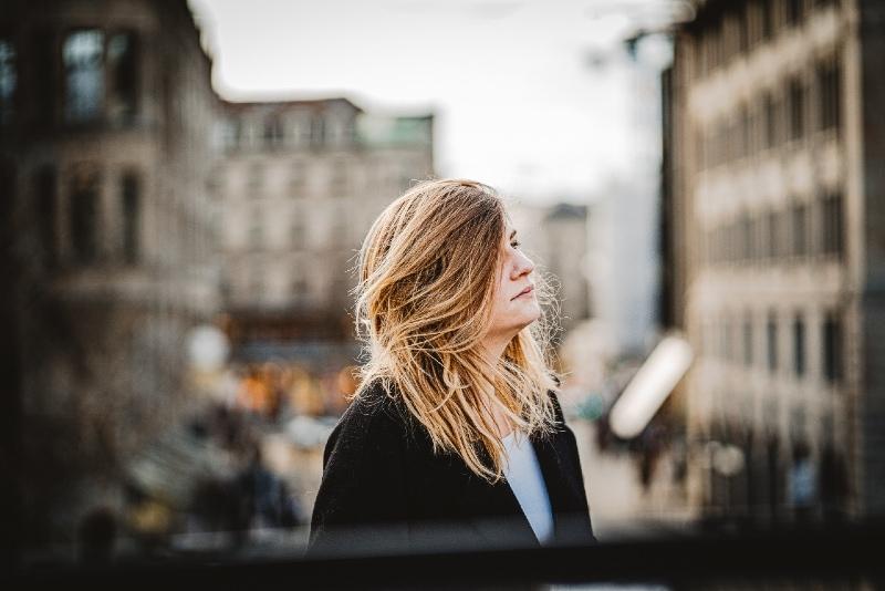 woman in black coat standing near building