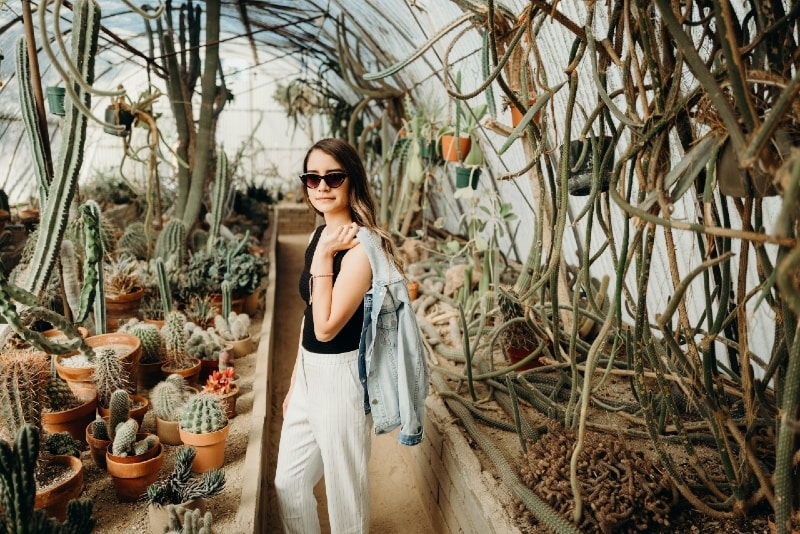 woman holding denim jacket while standing near plants