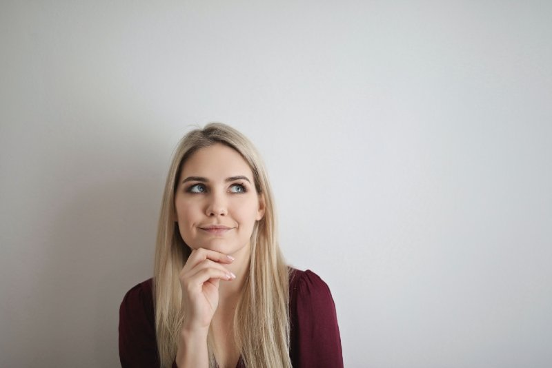 blonde woman in red blouse standing near wall and thinking