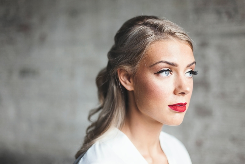 woman with red lipstick standing near wall