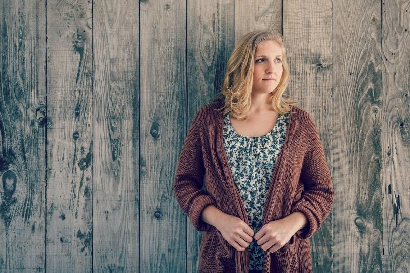 blonde woman standing near wooden wall