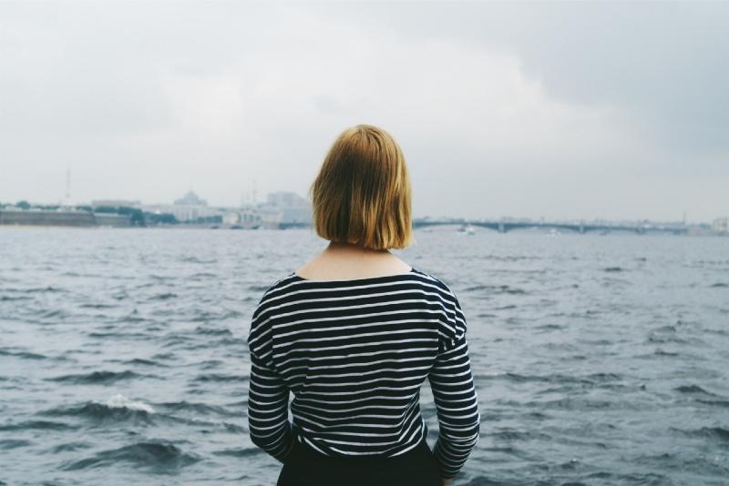 blonde woman in striped top standing near water