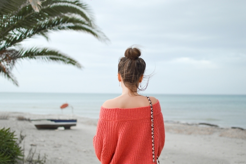 woman wearing red knitted sweater standing on beach