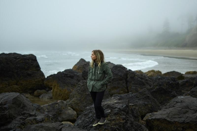woman in green jacket standing on rock