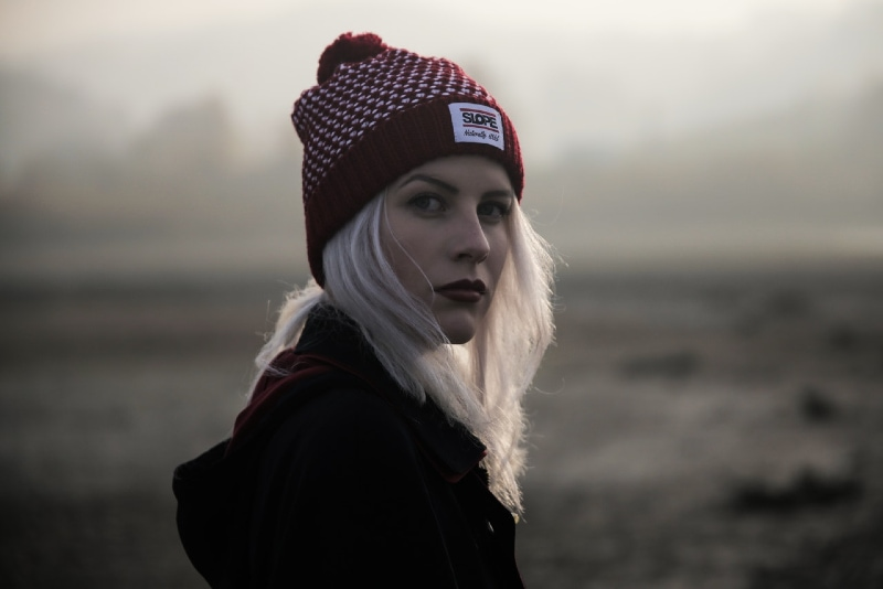 blonde woman with red knit cap standing outdoor
